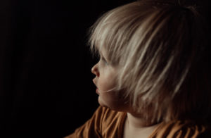 Profile of young child with a black background