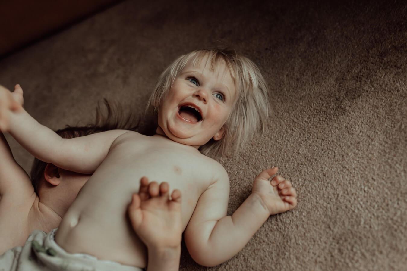 Toddler lies with her brother on the carpet during Melbourne's lockdown. She has blond hair and is laughing