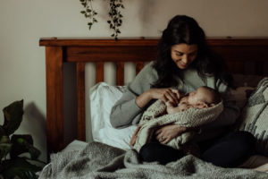 A young mother holds her newborn baby in her arms, sitting up in her bed at home
