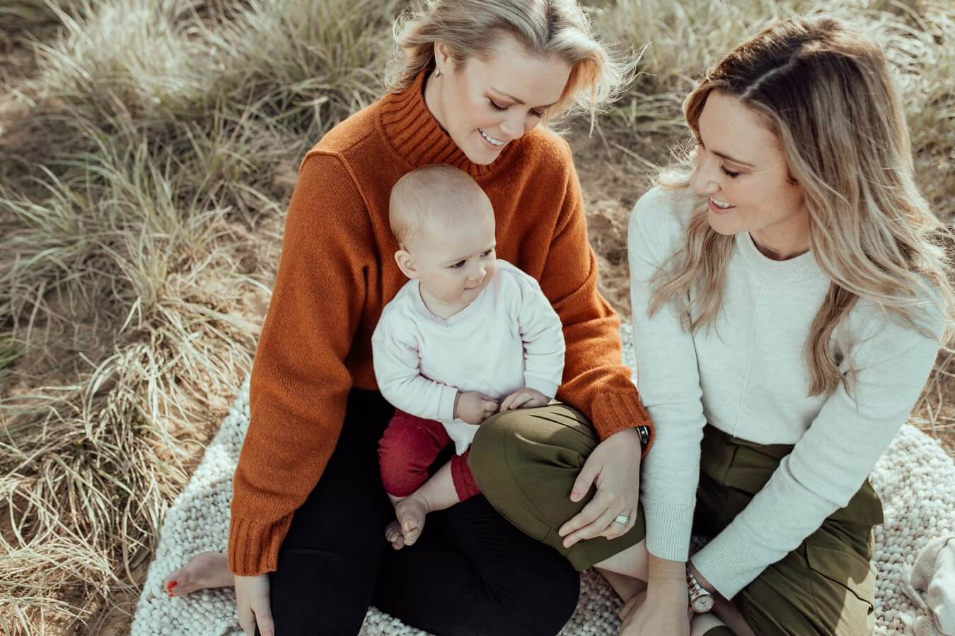 Two women sit outdoors on a blanket, smiling and looking down at a baby sitting in the lap of one woman. Taken by the beach at Ricketts Point, outside of Melbourne.
