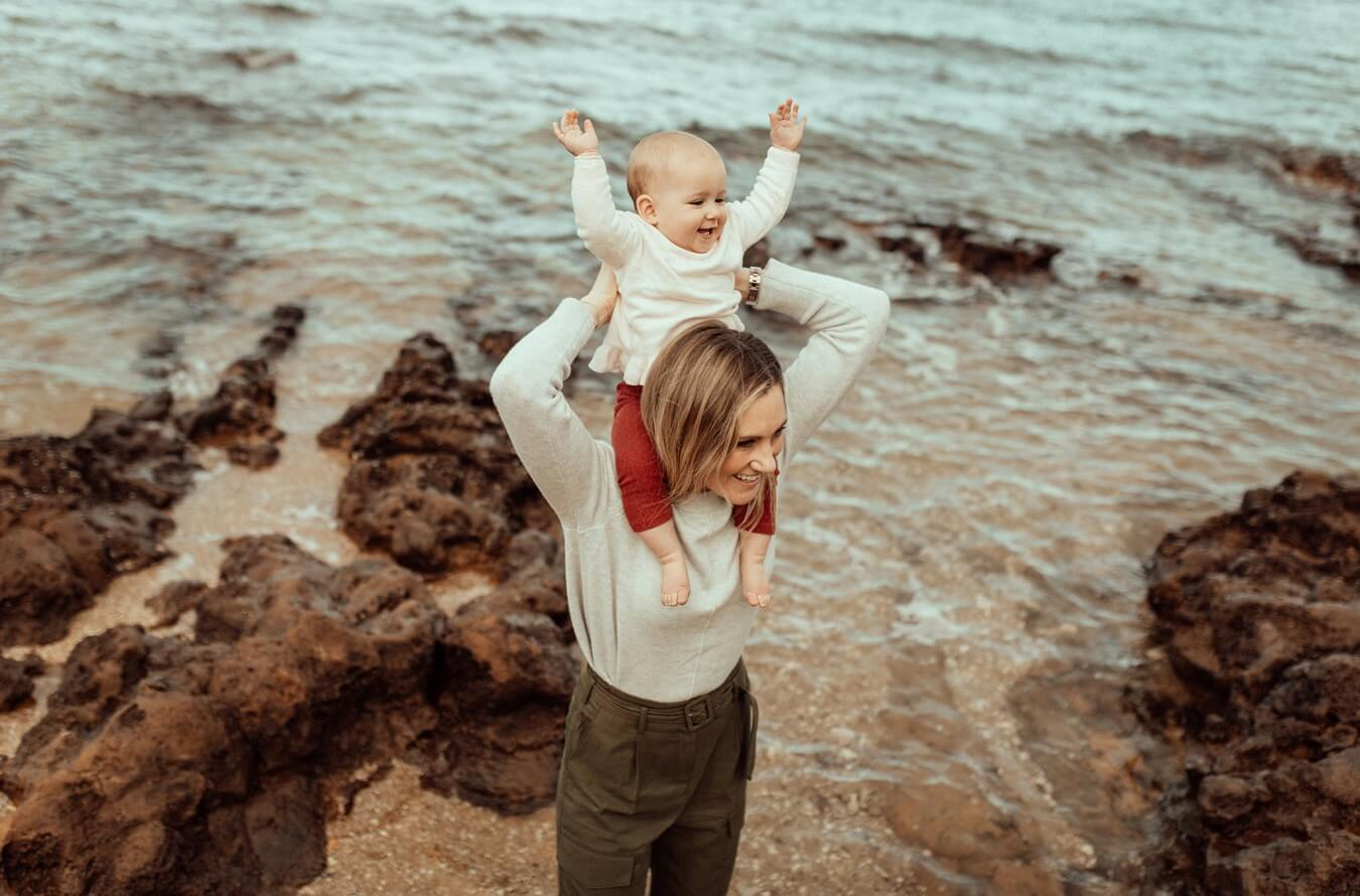 A mother stands by the waters edge at Ricketts Point beach with her baby on her shoulders. The child's arms are up in the air in joy.