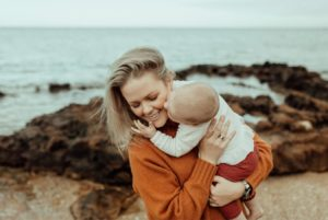 A mother stands on a rocky beach at Ricketts Point with her baby in her arms. The child is kissing its mother on the cheek.