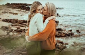 Two women embrace on the rocky beach at Ricketts Point. One is kissing the cheek of the other.