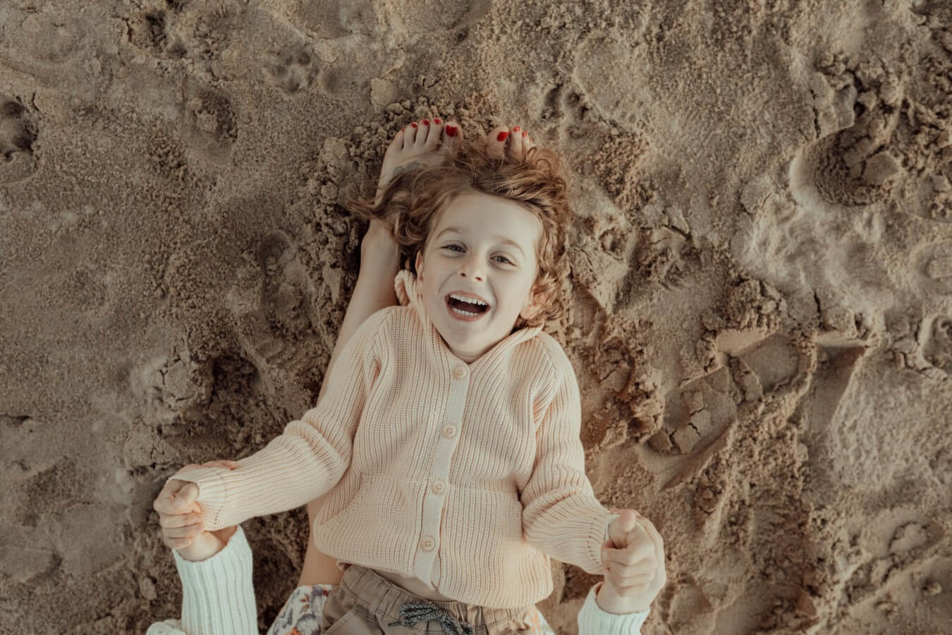 A young boy lies on the legs of his mother against the sand on the beach. His mother holds his hands while he laughs up at the camera.