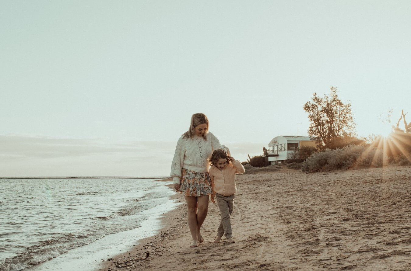 A mother and son walk along the water's edge on the beach at Ricketts Point. The sun is setting behind them.