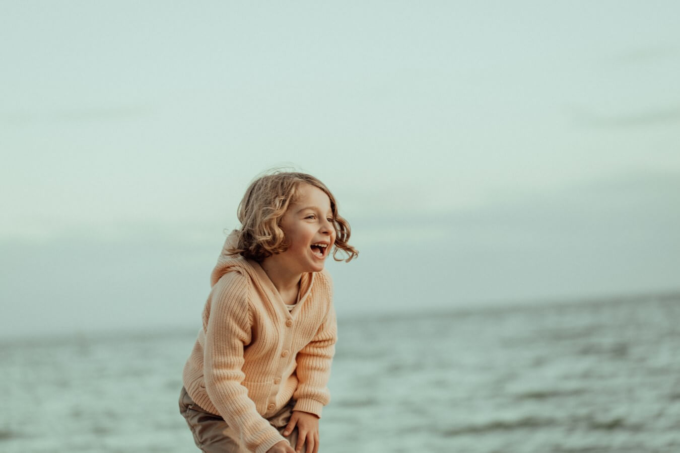 A young boy stands at the beach at Ricketts Point, laughing at something off camera. The water is in the background.