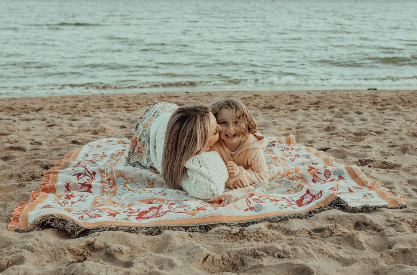 A mother and son cuddle on a blanket at the beach at Ricketts Point. The boy is looking at the camera while his mother kisses his cheek.